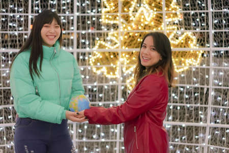 Teenagers celebrating the next travel experience. Happy young lesbian couple with the world in their hands. Travel and friendship concept.