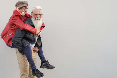 Retired couple playing to be young. Elderly couple having fun. Best elderly friends laughing at the camera. Retired and young concept. Standard-Bild