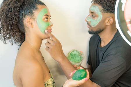 Man applying avocado mask on his girlfriend's face. Young couple taking care of skin at home. Health and spa concept.