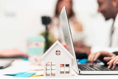 Closeup of white house and employees working with laptops in the office. Real estate value and cost concept. Technology, mortgage, rent and buy concept.