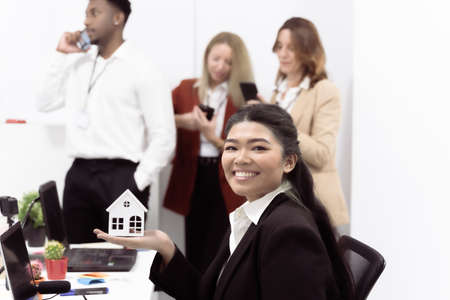 Real estate agent sustaining over hand a little white house, desktop with tools and laptops. Background there are business people working with smartphones. Technology, mortgage, rent and buy concept.