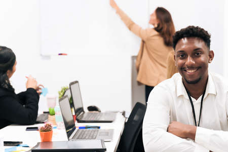 Young African male employee in formal clothes sitting in the office. Background teacher teaching. Job and university concept.