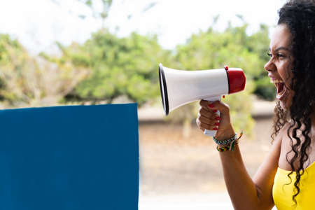 Funny young brunette woman girl screaming in megaphone. People sincere emotions lifestyle concept. Blue banner for copy space.