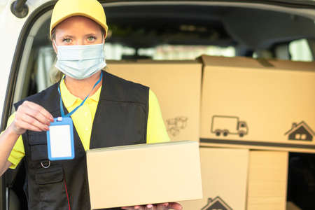 Portrait of woman courier with delivering package, with protective mask    . Copy space on blue identification card and package. Medical, delivery transport and express delivery. Standard-Bild