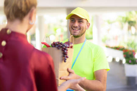 Handsome food delivery service man in yellow shirt holding fresh fruits and vegetables to customer at near home. Express delivery, takeaway food delivery and online shopping concept.