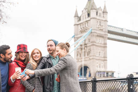 Happy group making a selfies near of Tower Bridge. University students traveling all over the world. Tourism, travel, people, leisure and teenage concept. Standard-Bild