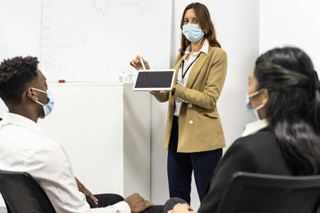 College tutor with digital tablet teaches young students. Real estate agent explaining rules to group of students in coronavirus time. Technology, teaching and covid 19 concept. Copy space Standard-Bild
