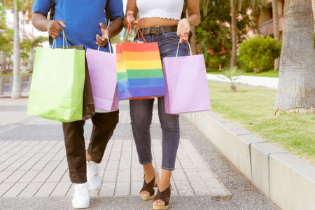 Midsection of couple with shopping bags in city. Two friends shopping together walking for the street. Buy, Sale, shop and black friday concept. Standard-Bild