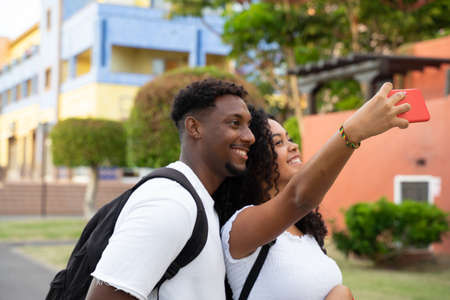 Younger couple making a selfie for new travel album. Technology and holiday concept. Focus on smartphone Standard-Bild