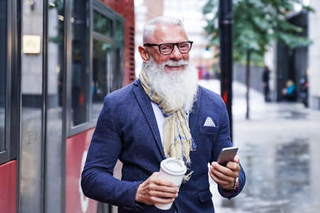 Business man using cellphone outdoors while waiting for the bus. Portrait of funny attractive cheerful pensioner hold hand hot takeout coffee beverage and smartphone. Transport and job concept.