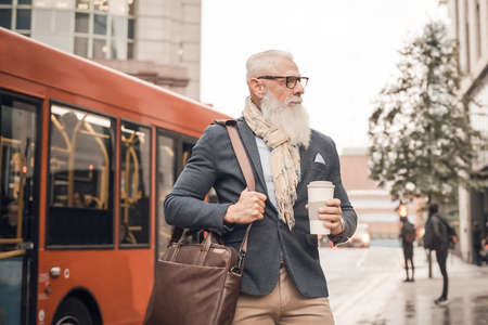 Portrait business man going to work. Serious hipster entrepreneur drinking coffee while waiting bus. Transport and job concept.