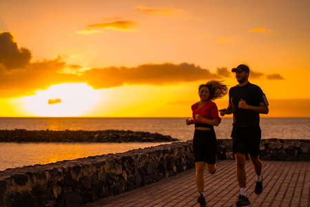 Runner athletes running at seaside. Fit runner fitness runner during outdoor workout with sunset background.