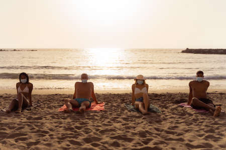 Multiracial friends with protective face mask and distancing in coronavirus time. Bored young millennial people sitting at beach in summer time. New normal lifestyle and social distancing concept.