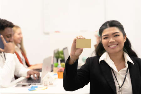 Happy smiling Asian business woman showing gold business card. Focus on gold card.
