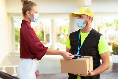 Deliveryman of goods and parcels to customers by protecting them with medical masks. Online shopping order under quarantine coronavirus covid-19.