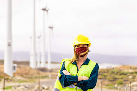 Front view of young woman engineer working in wind turbine farm. Clean energy, renewable energy and environment concept.