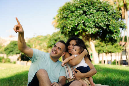 Family laughing during picnic in the park. Young cheerful family sitting on grass enjoying and playing with their baby. People having fun in summer park. Sunny day. Outdoor. Standard-Bild