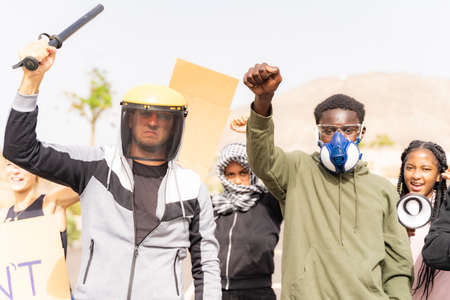 Multiethnic young people with raised fist shouting through megaphone and marched while being on anti-racism protest, coronavirus and no vax. Standard-Bild