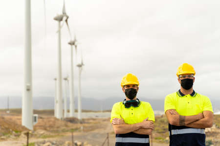 Front view of two skilled workers in a wind turbine power station. Two male electrician workers in reflective vests and hard hats. Clean energy, renewable energy and environment concept. Standard-Bild