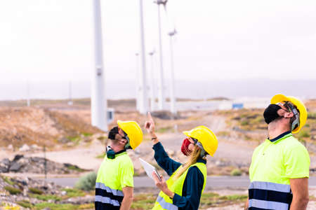 Woman engineer and skilled workers holding yellow safety helmet with standing and checking wind turbine power in construction site renewable energy. Clean energy and environment concept. Focus on face woman