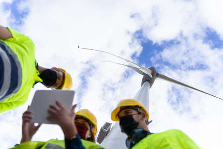 Engineer woman explaining being operated renewable energy with digital tablet. Concept of clean energy with wind turbines.