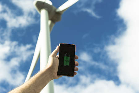 Hand portrait of caucasian man holding a smartphone, in the background a whirlwind. Renewable energy, future and electricity concept. Standard-Bild