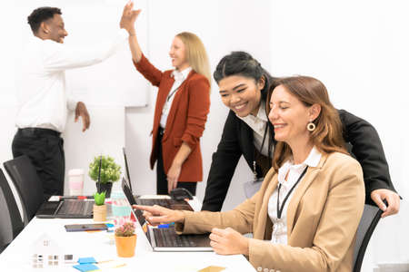 Group of multiracial business people working and communicating while sitting at the office desk together with colleagues high fiving in the background. Happy teacher explaining the lesson.