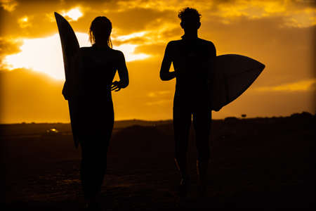 Silhouette young couple surfers stay on the sunset beach. Surfers walking with surfboards to the beach. Extreme sport, travel and vacation concept. Standard-Bild