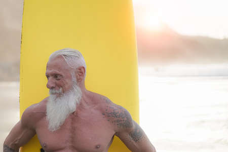 Sporty bearded man training with surfboard on the beach. Elderly healthy people lifestyle and extreme sport concept.