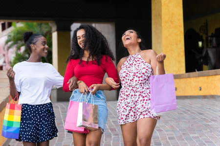 Happy young women coming out of shopping center. Sale, consumerism and people concept.