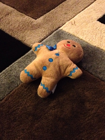 A stuff gingerbread man doll on the carpet floor  Imagens