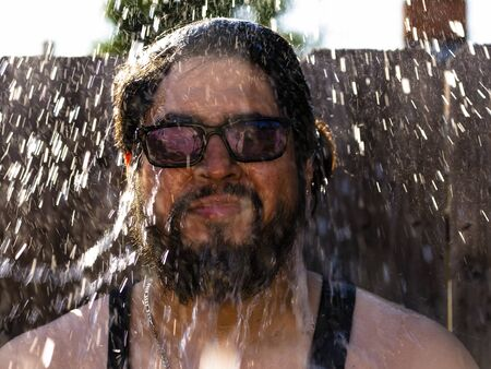 sunglasses wearing man drenched after a splash of water to face