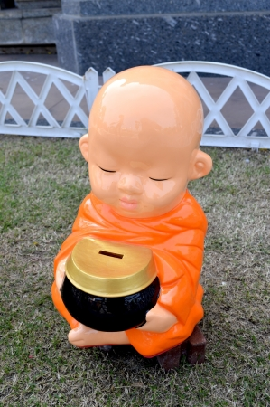alms: minifigura ni�o monje meditando sobre la hierba verde con las limosnas rueda