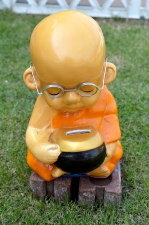 limosna: minifigura ni�o monje meditando sobre la hierba verde con las limosnas rueda