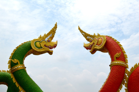 stair well: Green and red naga statue against blue sky