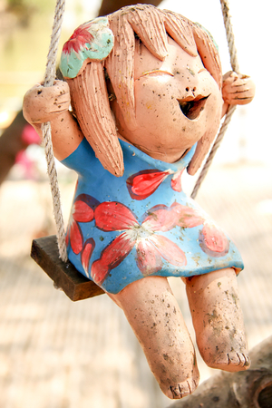 clay dolls  play the swings in the garden  Stock Photo
