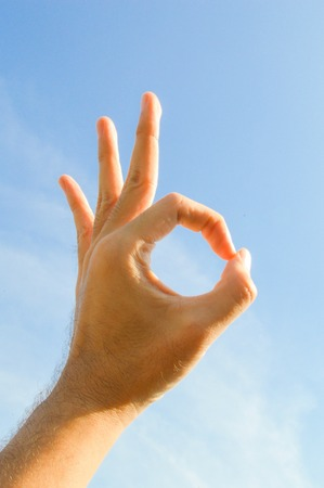Ok Sign (hand sign) on blue sky  photo