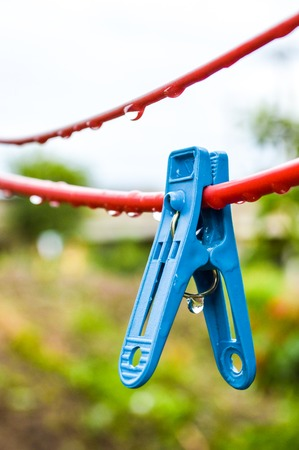 Blue Clothes pin on red hanger photo