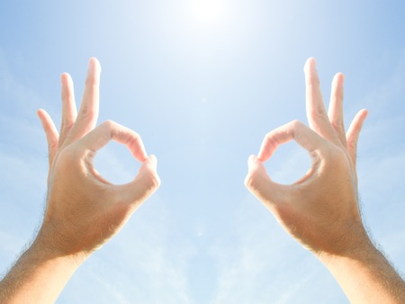 OK hand sign on blue sky