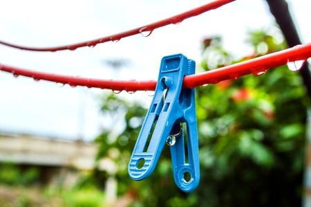 Blauwe wasknijper op rode hanger