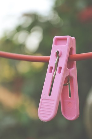 clothes pin: pink Clothes pin on red hanger Stock Photo