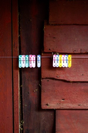 Clothes pin on wooden wall photo