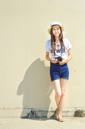 セメント壁のかわいいアジアの女の子の前面