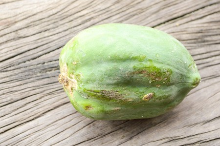 green papaya: green papaya on wooden floor