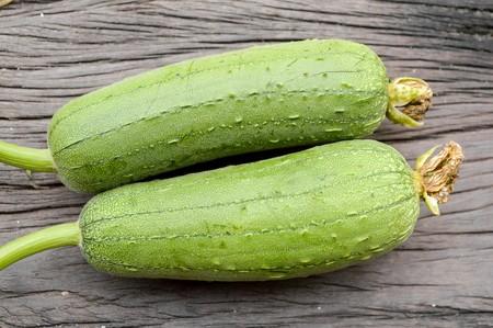 luffa: green Sponge Gourd on wooden floor (Luffa cylindrica) Stock Photo
