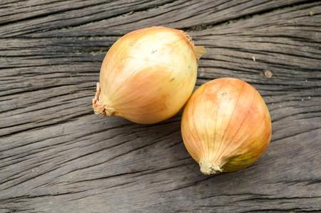 allium: Onion on wooden floor (Allium cepa Linn.) Stock Photo
