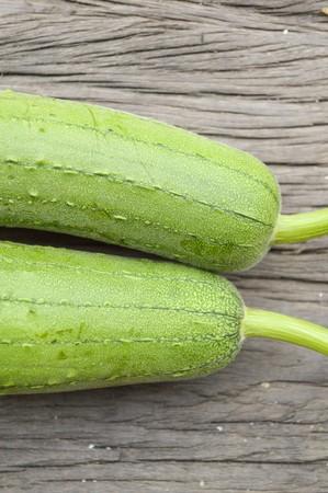 cylindrica: green Sponge Gourd on wooden floor (Luffa cylindrica) Stock Photo