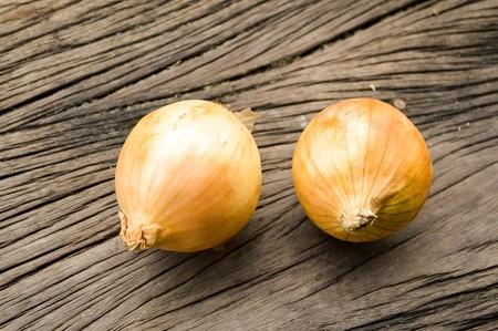 allium cepa: Onion on wooden floor Allium cepa Linn.