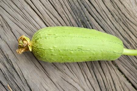 cylindrica: green Sponge Gourd on wooden floor Luffa cylindrica Stock Photo