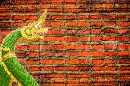 green nagas statue on old brick wall background